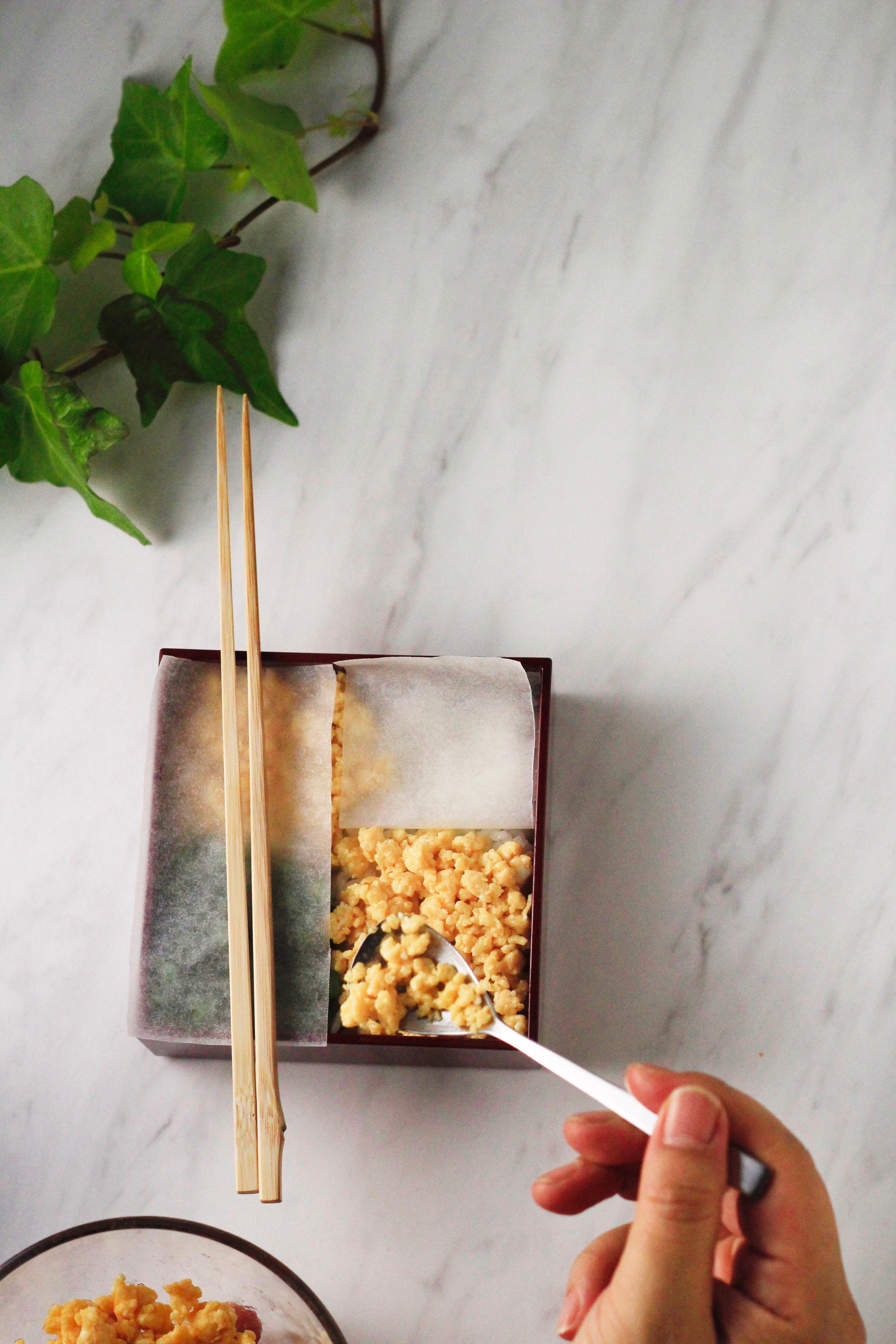そぼろ弁当盛り付け⑧盛り付ける時にシートがめくれてしまう場合は、お箸などで抑えて